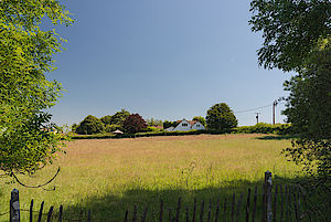 view across field to cottage